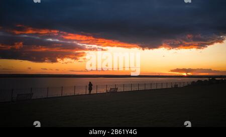 Sunset over the sea. A lady watches from behind a fence with grass in the foreground - Stock Photo