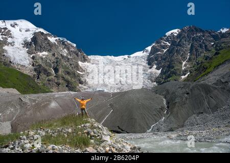 Woman dressed in bright orange wind jacket against icefall background. Beautiful sunny day in high mountains.