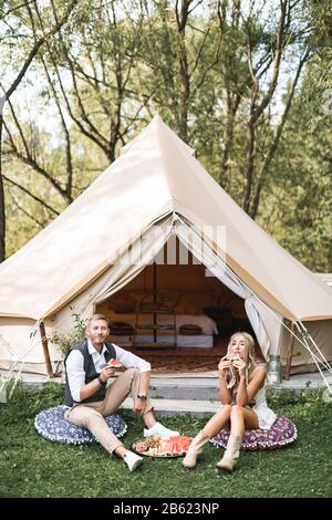 Summer picnic at sunset. Young couple wearing stylish boho casual clothes sitting on the pillows on green grass in front of big wigwam tent outdoors - Stock Photo