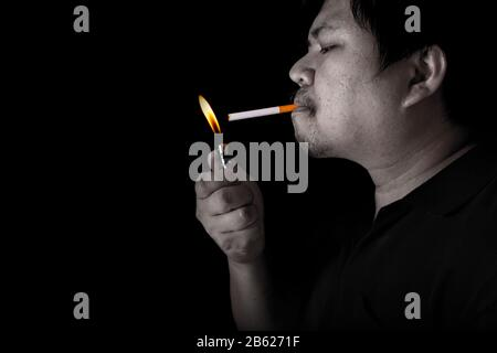 The fat man lighting up a joint with lighter smoking at the black background, close up image of cigarette smoke spread in hand - Stock Photo