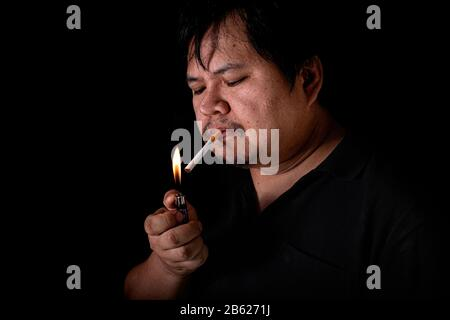 The fat man lighting up a joint with lighter smoking at the black background, Image of cigarette smoke spread in hand - Stock Photo