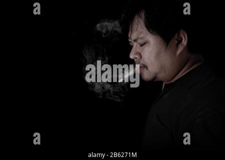 The fat man was wearing a black shirt smoking at the black background, Image of cigarette smoke spread in hand - Stock Photo