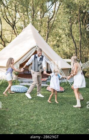 Young stylish family with children have fun in a park. Father, mother and daughters dancing in nature together, holding hands. Family dancing near
