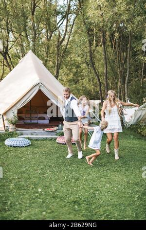 Happy family: mother, father, two children daughters on nature, dancing and running together. Cheerful family in boho light clothes