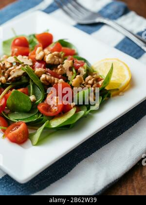 Winter purslane salad with tomatoes and toasted walnuts. - Stock Photo