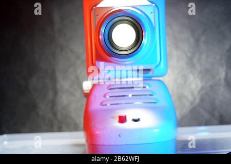 Old slide projector with slide frame photographed in the studio with flash light