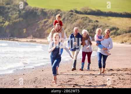 Multi-Generation Family Walking Along Shoreline Of Beach By Waves Together