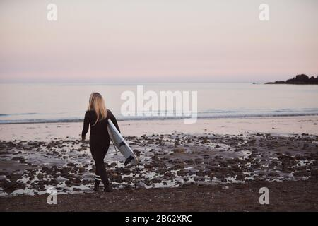 Woman Wearing Wetsuit Carrying Surfboard As She Walks Into Sea - Stock Photo
