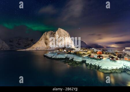 Beautiful Northern Lights in Hamnoy, Lofoten Island in Norway. Aurora Boreal over the small fishing village with its traditional red huts. Majestic gr