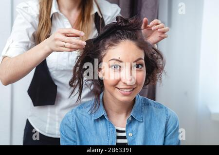 Hair stylist making ringlets to a happy brunette woman. Hairdresser working with brunette woman hair in hairdressing salon. Close up view