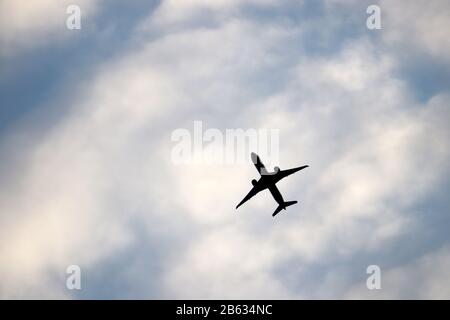 Airplane flying in the blue sky on background of white clouds. Silhouette of a commercial plane during the climb, travel and turbulence concept