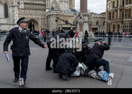 Pro-Democracy protesters with a Free Southern Cameroon group are tackled by Metropolitan police officers after dashing out from behind barriers outside Westminster Abbey during the Commonwealth Day service lead by the Queen and including members of the British royal family and Commonwealth ambassadors and dignitaries. They are holding placards saying Free President Ayuktabe Julius' (an Ambazonian separatist leader) and 'Justice for Babanki' (referring to allegations of soldier killings on villagers), on 9th March 2020, in London, England. At this, their last royal duty before stepping down for - Stock Photo