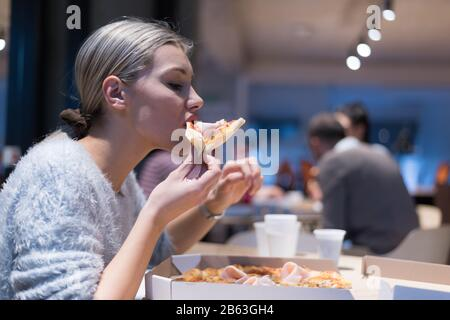 beautiful woman eating pizza and drinking cola while sitting inside expres restaurant late at night 2b63gh4