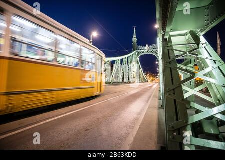 Night view of a tram crossing the Liberty Bridge in Budapest, Hungary. - Stock Photo