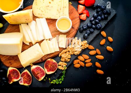 Cheese plate. Assortment of cheese with walnuts, almonds, grapes, figs, strawberries blueberries and honey - Stock Photo