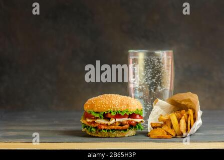 Carbonated sweet drink in a glass and hamburger, salty snacks, pretzels, chips. - Stock Photo