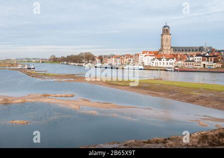 DEVENTER, THE NETHERLANDS - JANUARY 18, 2014: The historic center of Deventer with the Lebuinus Church and the river IJssel in the foreground. - Stock Photo