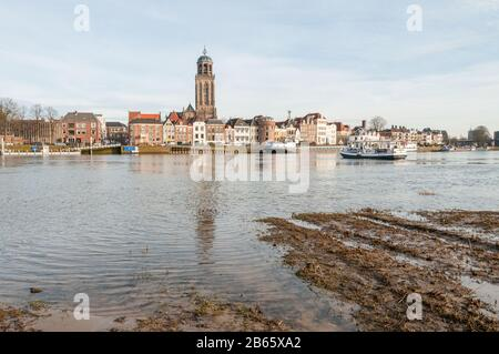 DEVENTER, THE NETHERLANDS - JANUARY 18, 2014: The historic center of Deventer with the Lebuinus Church and the river IJssel in the foreground. The fer - Stock Photo