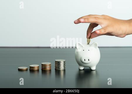 Money saving and donation concept, child put money on cute white piggy bank