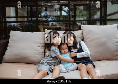 Asian children smile when sitting on the sofa hugging each other - Stock Photo