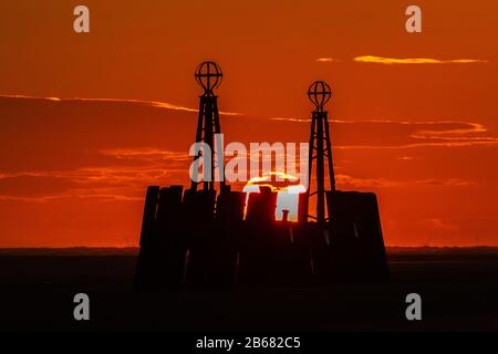 the sun sets in a deep red sky between the two pillars of the landing jetty of st annes pier - Stock Photo