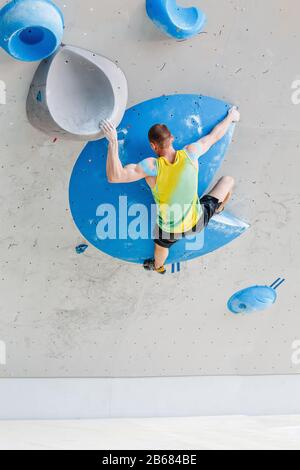 Sport and fitness Man on Extreme Climbing Wall boulder gym - Stock Photo