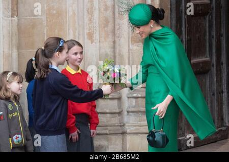 London, Britain. 9th Mar, 2020. Meghan Markle, Duchess of Sussex, is presented with flowers by children after attending the annual Commonwealth Service at Westminster Abbey on Commonwealth Day in London, Britain, March 9, 2020. Credit: Ray Tang/Xinhua/Alamy Live News - Stock Photo