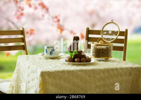 Beautiful served small table with Easter decorations on outdoor terrace. Little chocolate bunny with bow, chocolate eggs, cup of coffee, crystal bowl. - Stock Photo