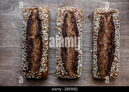High angle close up of three freshly baked seeded loaves of bread in an artisan bakery. - Stock Photo