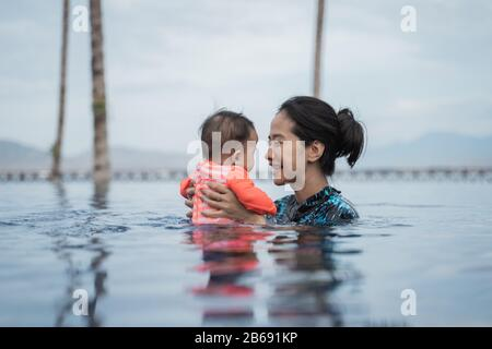 mother holding her child while swimming in the pool while enjoying playing together - Stock Photo