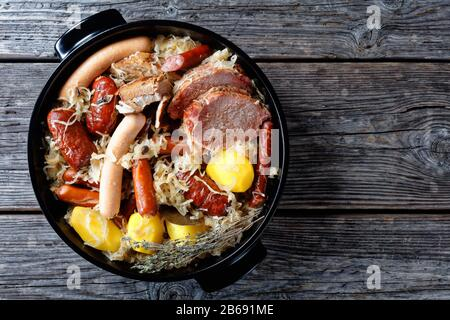 French choucroute garnie of sour cabbage with smoked bacon, pork loin, sausages potato and thyme stewed in white wine with onion, garlic served on a b - Stock Photo