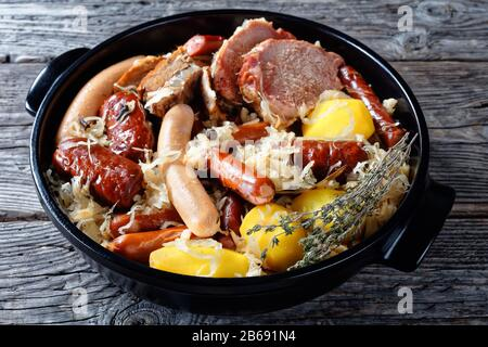 Alsace dish: sour cabbage stew with meat: pork loin and bacon and sausages and potato cooked in white wine thyme, juniper berries, garlic served on a - Stock Photo