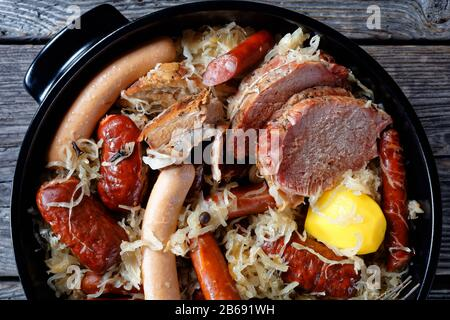 Sour cabbage stew with different types of meat and sausages and potato stewed in white wine with onion thyme juniper berries, garlic served on a black - Stock Photo