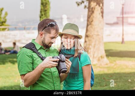 Couple of tourists reviewing photos in a dslr camera in park, learning photo together concept - Stock Photo