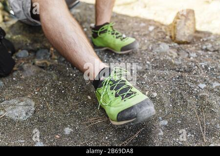 Green low modern Hiking shoes closeup on man feet - Stock Photo