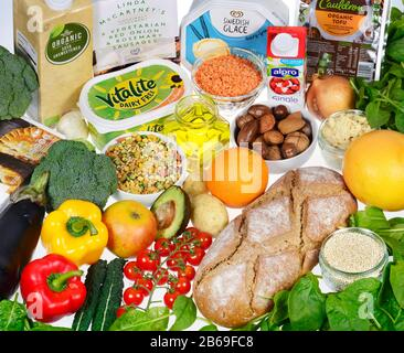 Vegan foods, including bread, fresh fruit and vegetables, plant-based alternatives to dairy, grains, pulses, and meat-free products - Stock Photo