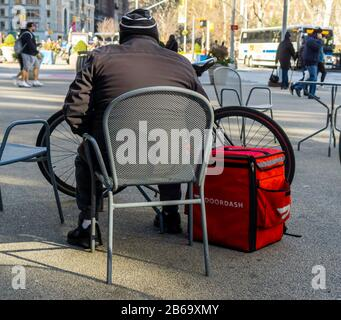A delivery person with a DoorDash branded tote waits for his next job in the Chelsea neighborhood of New York on Saturday, March 7, 2020. (© Richard B. Levine) - Stock Photo