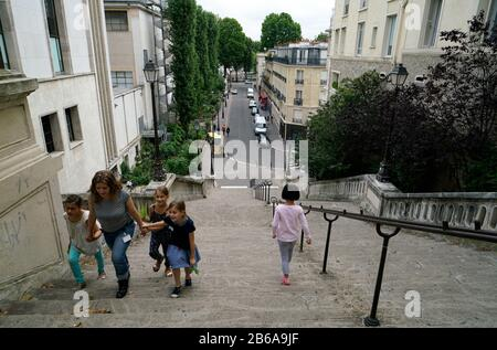Adult and children walking on the steep Rue de la Manutention connecting River Seine and Avenue du President Wilson in 16th arrondissement.Paris.France - Stock Photo