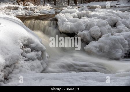 Ocqueoc Falls flows through snow and ice under winter conditions near Rogers City in Northern Lower Michigan - Stock Photo