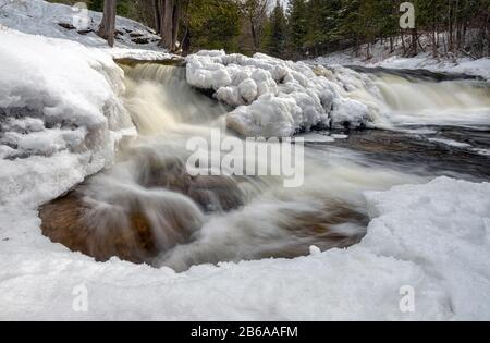 Ocqueoc Falls flows through ice and snow near Rogers City in Northern Lower Michigan during a cold winter - Stock Photo