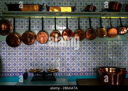 copper pots and pans on the wall of the kitchen of Claude Monet House in Giverny.region of Normandy.France - Stock Photo