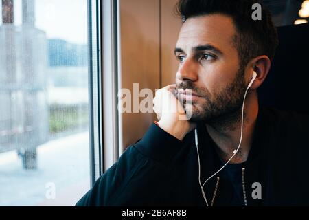 Young man traveling by train wearing earphones - Stock Photo