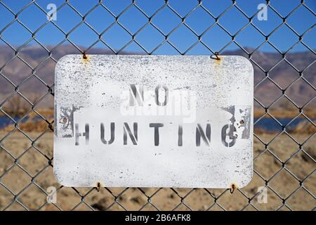 no hunting sign wired to a chain link fence - Stock Photo