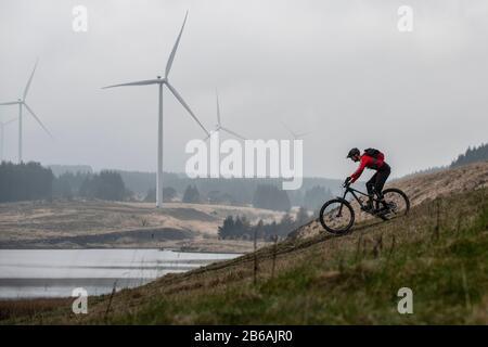 Two men ride mountain bikes in the shadow of wind turbines near Lluest-Wen Reservoir in South Wales.