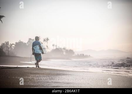Surfer on a beach headed towards the ocean. - Stock Photo