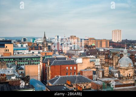 A wide rooftop view looking out over the buildings and architecture of Glasgow city centre in evening light, Scotland