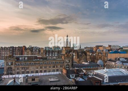 A wide rooftop view looking out over the buildings and architecture of Glasgow city centre at sunset, Scotland