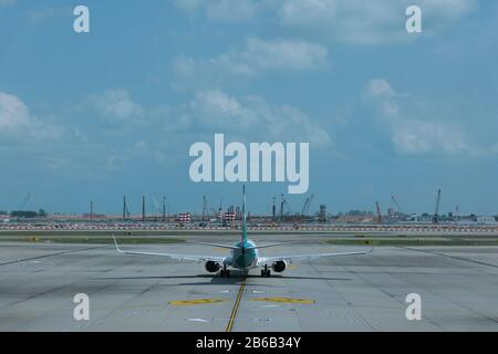 airplane on airport runway under dramatic sky in Singapore airport