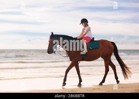 Kids riding horse on beach. Children ride horses. Cute little girl on pony on a ranch. Child and animal. Kid in safe helmet for horseback class. Trave