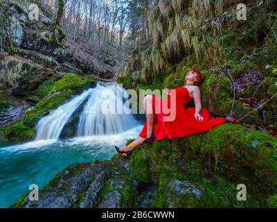 Fanciful woman wearing long Red dress legs heels in nature reclining near flowing water waterfall Green forest - Stock Photo
